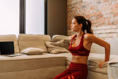 Photo pour Belle sportive formation en ligne et faire pousser vers le haut sur le canapé pendant l'isolement personnel - image libre de droit