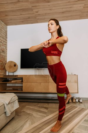 attractive sportswoman training online with resistance band on fitness mat at home during self isolation