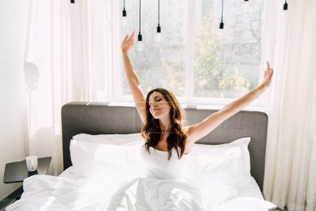 Photo for Attractive happy woman stretching on bed in morning during quarantine - Royalty Free Image