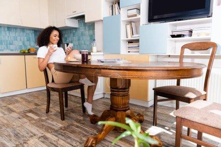 glücklich afrikanisch-amerikanische Frau mit Tasse Kaffee und Smartphone in der Nähe von leckerem Frühstück und Fernseher mit leerem Bildschirm