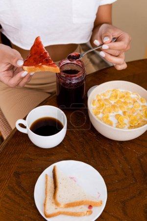 Photo pour Vue recadrée d'une femme afro-américaine tenant une cuillère avec de la confiture près de pain grillé, des flocons de maïs dans un bol et une tasse avec café sur la table - image libre de droit