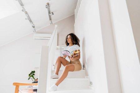Photo pour Jeune femme afro-américaine assis sur les escaliers avec magazine - image libre de droit