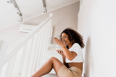 Photo pour Happy african american woman sitting on stairs and holding bowl with breakfast - image libre de droit