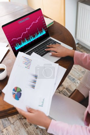 Photo for Cropped view of african american freelancer holding charts and graphs near laptop with  trading on screen - Royalty Free Image