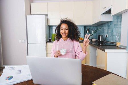 Photo pour Heureux afro-américaine fille montrant signe de paix et tenant tasse tout en ayant chat vidéo à la maison - image libre de droit