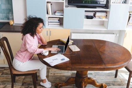Photo pour Frisé afro-américain pigiste à l'aide d'un ordinateur portable près de tasse, livres et documents - image libre de droit