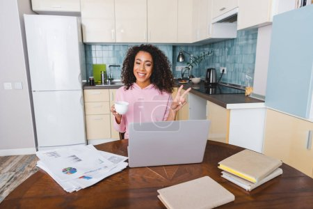 Photo for Happy african american girl showing peace sign while holding cup and having video chat at home - Royalty Free Image