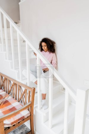 Photo pour African american freelancer sitting on stairs while using laptop and holding smartphone - image libre de droit
