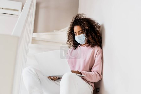 Photo pour Curly african american freelancer in medical mask sitting on stairs and using laptop - image libre de droit