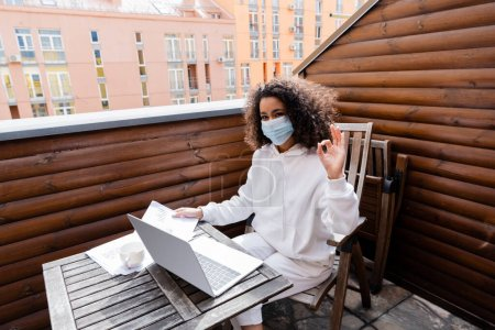 Photo for African american girl in medical mask showing ok sign near laptop, cup, charts and graphs - Royalty Free Image