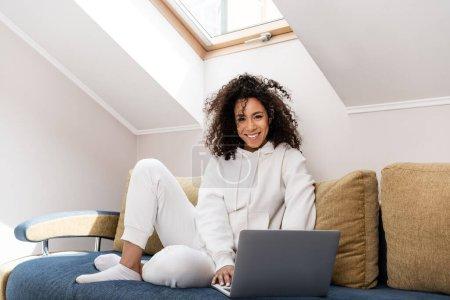 Photo pour Joyeux afro-américain freelance assis sur le canapé et en utilisant un ordinateur portable à la maison - image libre de droit