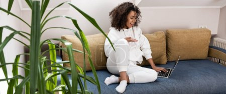 panoramic shot of happy african american girl sitting on sofa and gesturing near laptop while having video call