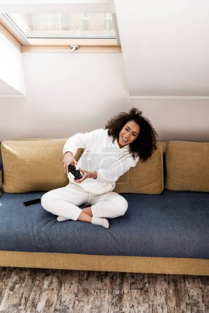 Photo for KYIV, UKRAINE - APRIL 15, 2020: cheerful african american girl playing video game at home - Royalty Free Image