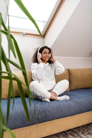 Photo for Selective focus of happy african american girl touching wireless headphones while sitting on sofa - Royalty Free Image