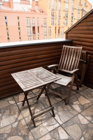 Photo for Wooden chair and table on modern balcony - Royalty Free Image
