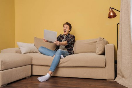 Photo for Excited freelancer holding laptop in living room - Royalty Free Image