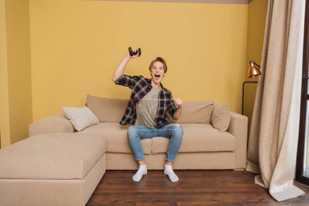 KYIV, UKRAINE - APRIL 24, 2020: excited man holding joystick while playing video game in living room