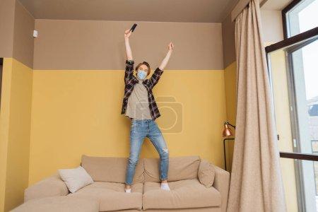 Photo pour Homme en masque médical debout sur le canapé et tenant la télécommande au-dessus de la tête, fin du concept de quarantaine - image libre de droit