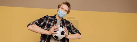 panoramic concept of man in medical mask holding football, end of quarantine concept