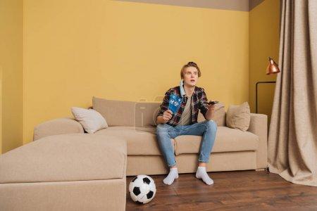 Foto de Emotivo hombre en la máscara médica que tiene entradas para partidos deportivos cerca del fútbol mientras ve campeonato en casa. - Imagen libre de derechos