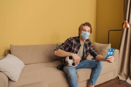 Foto de Sorprendido hombre en la máscara médica que tiene entradas para partidos de fútbol y deporte, fin del concepto de cuarentena. - Imagen libre de derechos