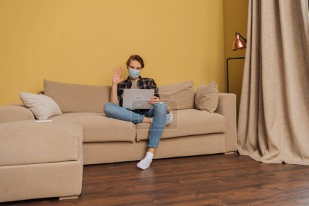 Mann mit medizinischer Maske winkt bei Videochat im Wohnzimmer