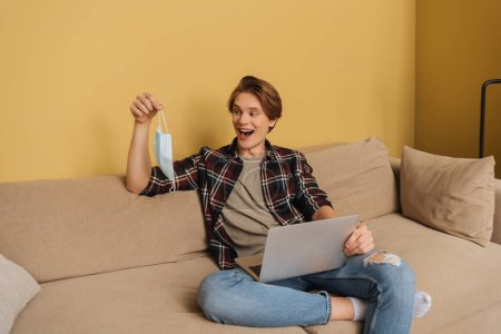 happy freelancer holding medical mask near laptop in living room, end of quarantine concept