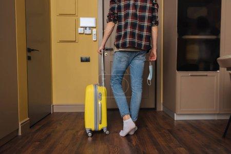 Photo pour Vue recadrée de l'homme tenant un masque médical et marchant avec ses bagages, concept de fin de quarantaine - image libre de droit