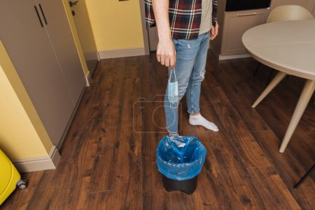 Photo for Cropped view of man holding medical mask near trash can with garbage bag, end of quarantine concept - Royalty Free Image