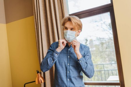 young man touching medical mask at home