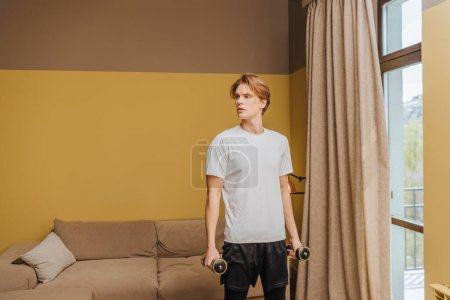 handsome young man exercising with dumbbells in living room, end of quarantine concept