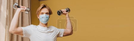 Photo for Panoramic orientation of man in medical mask exercising with dumbbells in living room - Royalty Free Image