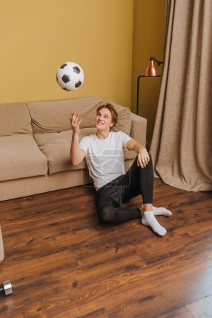 happy man throwing in air football at home, end of quarantine concept