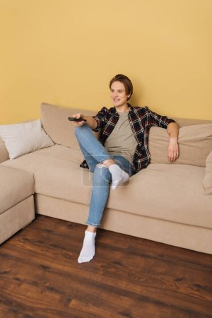 cheerful man holding remote controller and sitting on sofa, end of quarantine concept