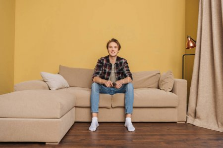 smiling man holding remote controller and sitting on sofa, end of quarantine concept
