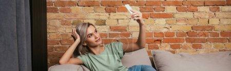 Photo pour Plan panoramique de belle jeune femme prenant selfie sur smartphone tout en se relaxant sur canapé - image libre de droit