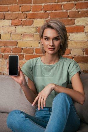 schöne junge Frau sitzt auf Sofa in der Nähe Ziegelwand und zeigt Smartphone mit leerem Bildschirm