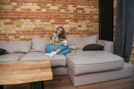 attractive young woman holding cup of tea while sitting on sofa near brick wall