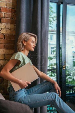 Photo pour Vue latérale de femme coûteuse tenant ordinateur portable tout en étant assis près de la fenêtre à la maison - image libre de droit