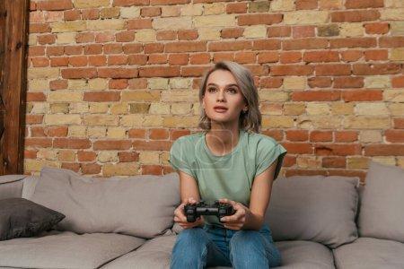 Photo pour KYIV, UKRAINE - 30 AVRIL 2020 : jeune femme concentrée jouant à un jeu vidéo avec joystick à la maison - image libre de droit