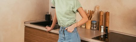 cropped view of woman holding hand in pocket while standing in kitchen, panoramic shot