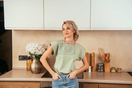 Photo pour Belle femme souriante regardant dehors debout, les mains dans les poches dans la cuisine - image libre de droit
