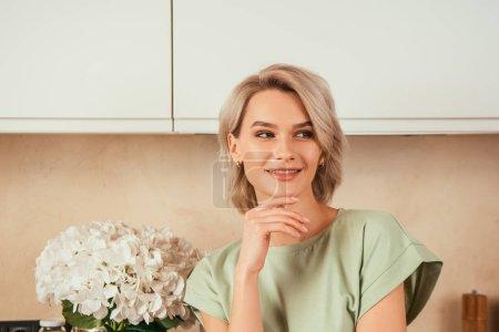 Photo pour Femme positive et séduisante se touchant le visage et regardant loin dans la cuisine - image libre de droit
