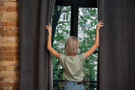 Photo for Back view of young woman opening dark curtains on window at home - Royalty Free Image