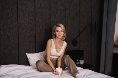 Photo pour Happy, attractive woman looking at camera while sitting in bed with cup of tea - image libre de droit