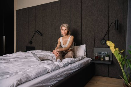 Photo for Attractive woman looking at camera while sitting on bed near laptop - Royalty Free Image
