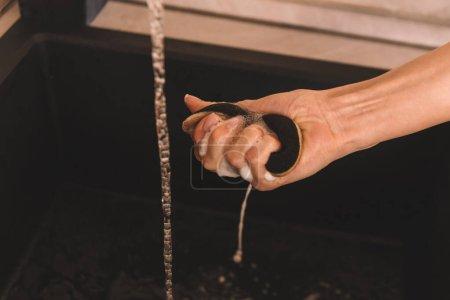 Photo pour Vue recadrée de la main féminine avec éponge savonneuse humide - image libre de droit