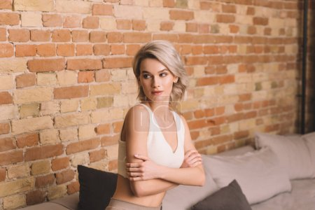 Photo for Attractive young woman sitting on sofa near brick wall with crossed arms and looking away at home - Royalty Free Image