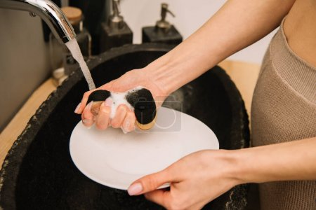 cropped view of woman washing white plate with sponge