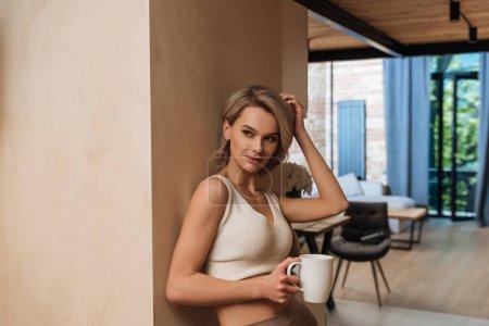 Photo pour Belle femme tenant une tasse de thé et touchant les cheveux tout en se tenant près du mur et en regardant loin de la maison - image libre de droit